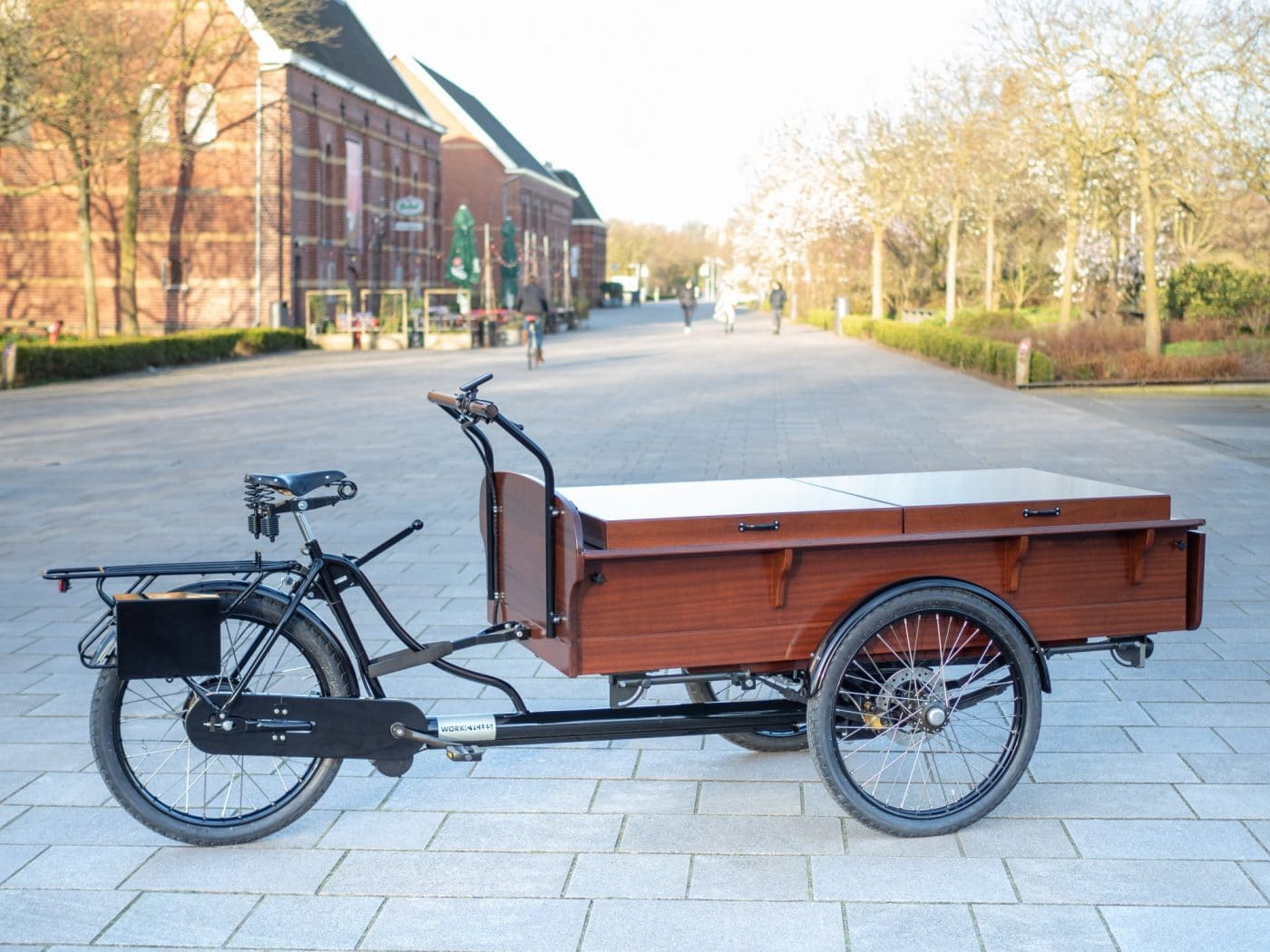 """The beautiful, old-fashioned Dutch """"bakfiets"""" cargo trike comes in three different sizes; M, L and XL. The size Large trike is both shorter and narrower than the enormous """"XL"""" so it can typically be ridden in a bike path and fits between bollards. Aside from the dimensions the M, L and XL are technically identical."""